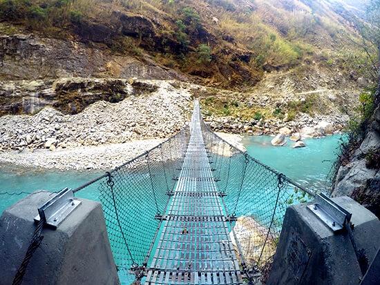 Crossing river on bridge on the Annapurna Circuit Trek
